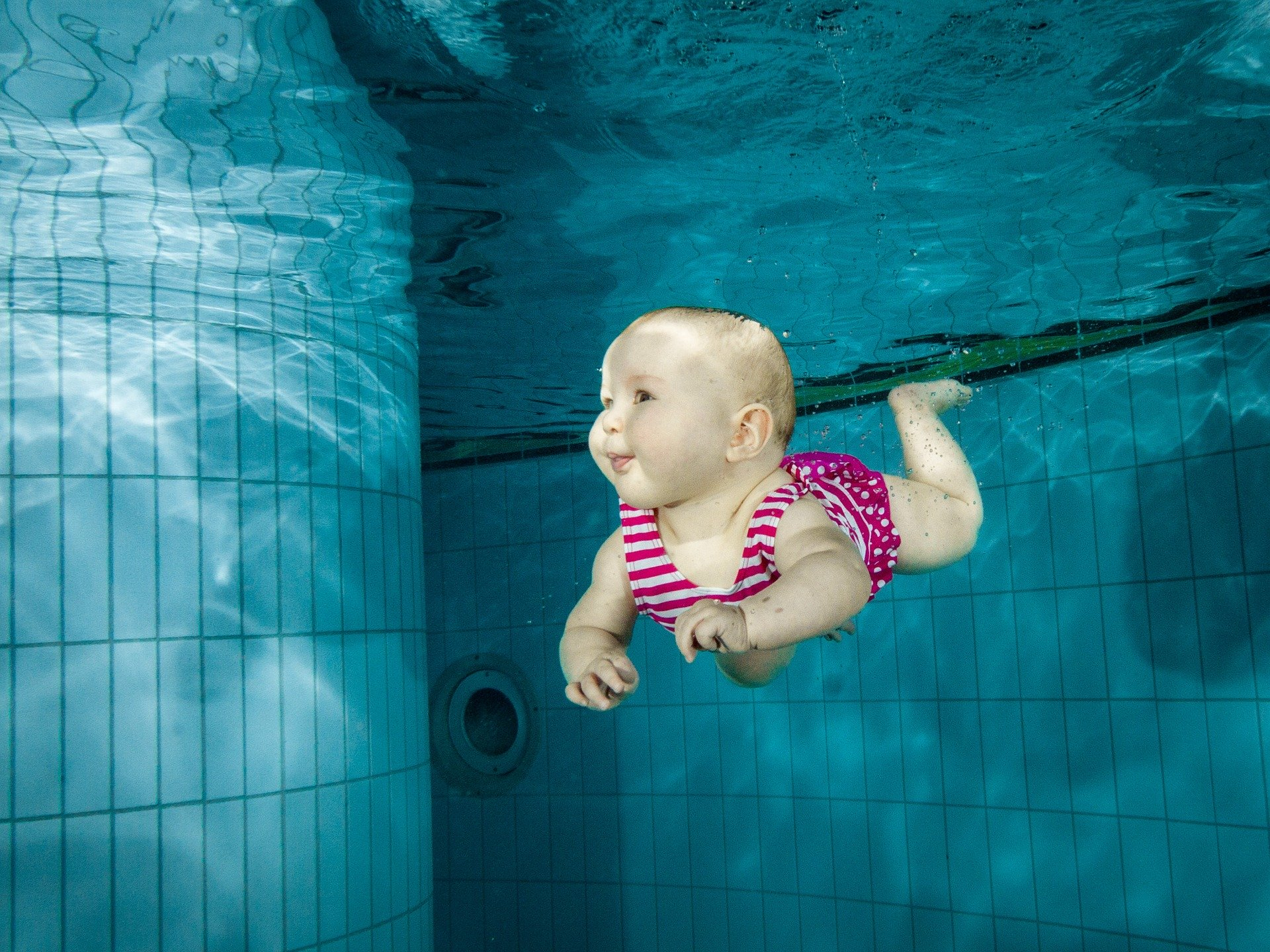 Vauva sukeltaa uima-altaassa.