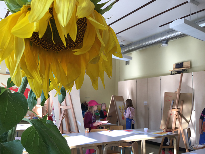 Auringonkukka ja lapsia maalaamassa