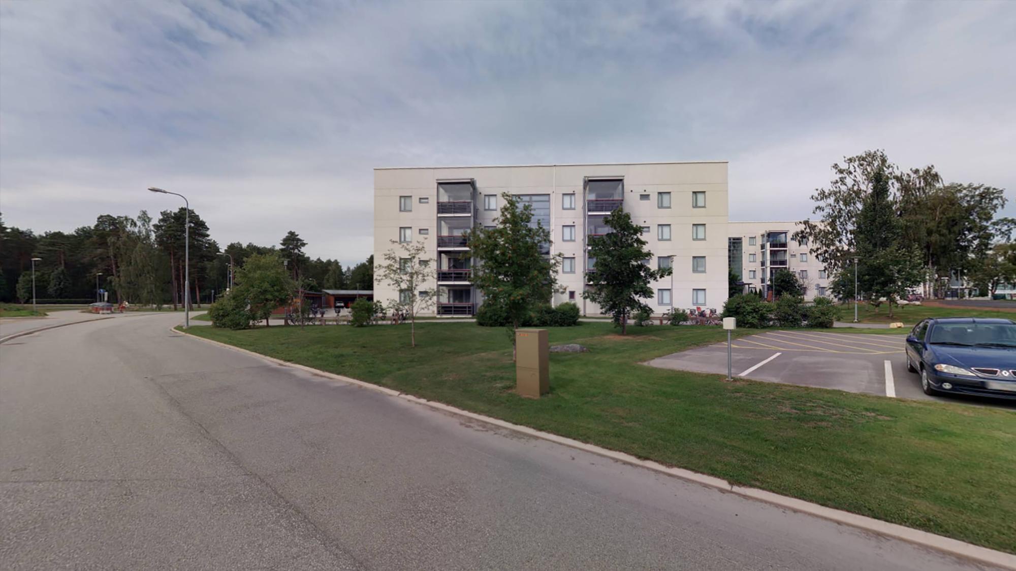 Ett ljust hyreshus i fyra våningar på Kanonvägen i Beckbruket fotat från vägen framför huset. Framför huset finns en gräsmatta och små buskar. I bakgrunden syns ett annat ljust våningshus.