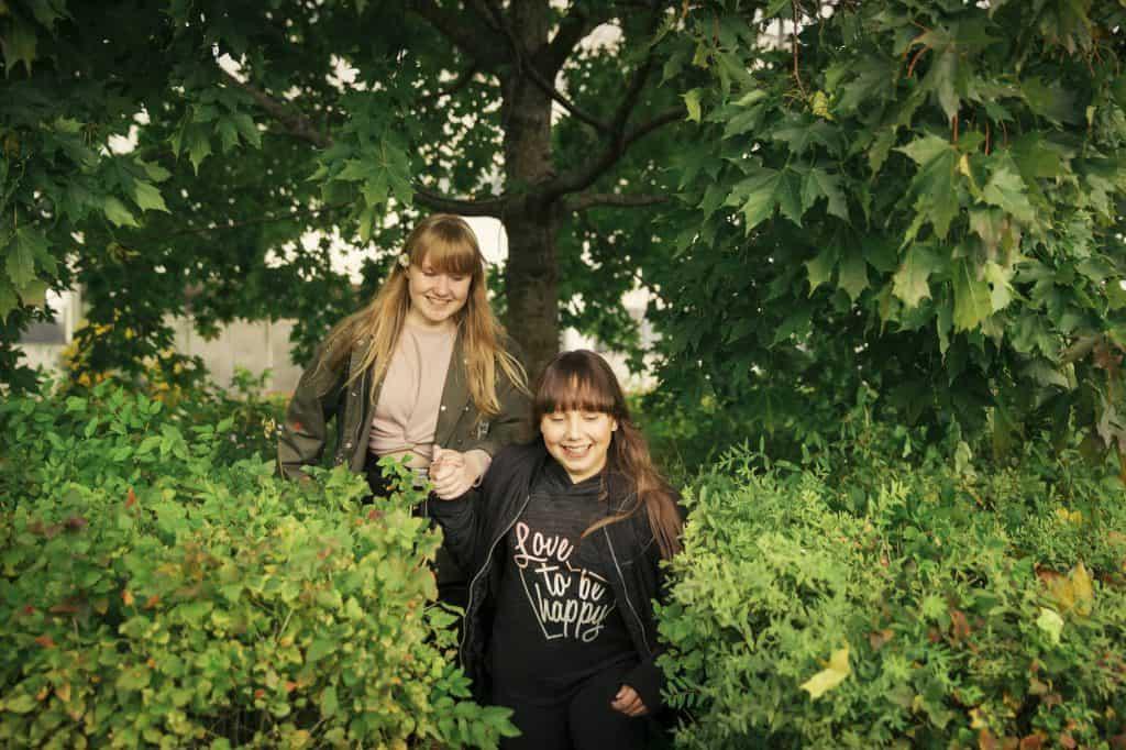 Två flickor skrattar i naturen.