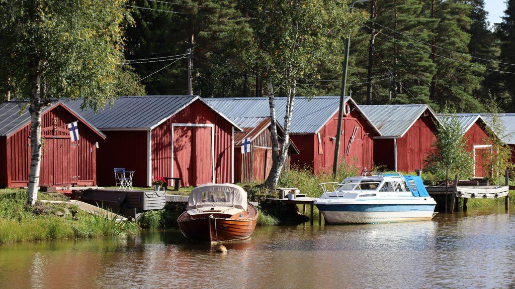 Sunti ja sen takana olevia punaisia venevajoja. Venevajojen edessä on kaksi laituriin kiinnitettyä venettä.