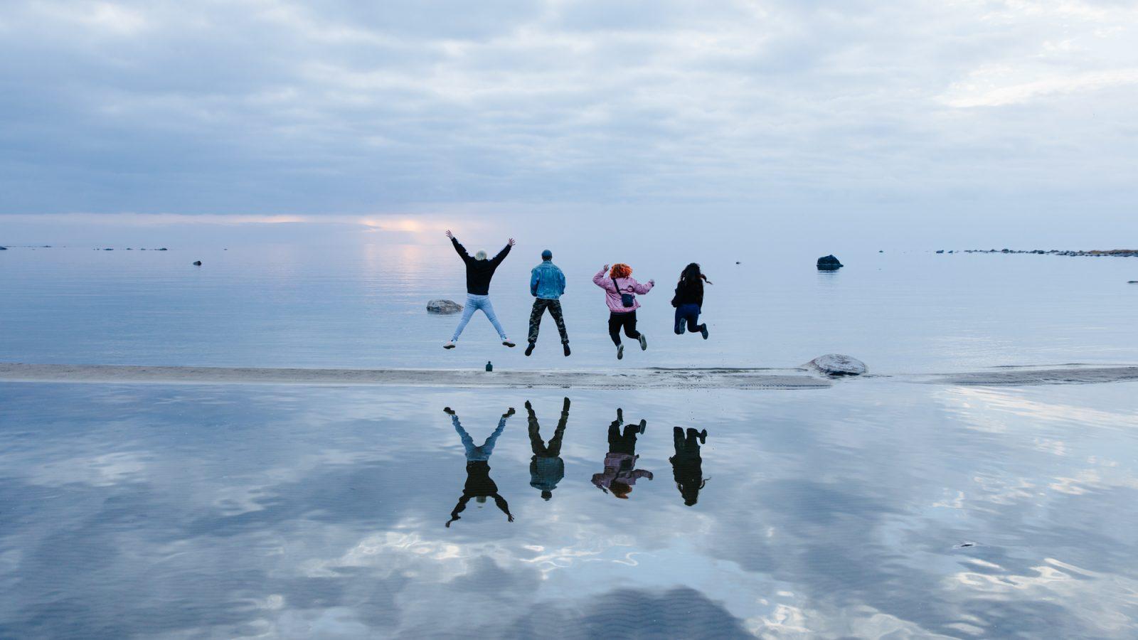 Ihmiset hyppäävät rantahiekalla