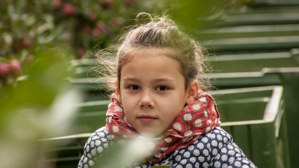 Tyttö, taustalla omenapuu