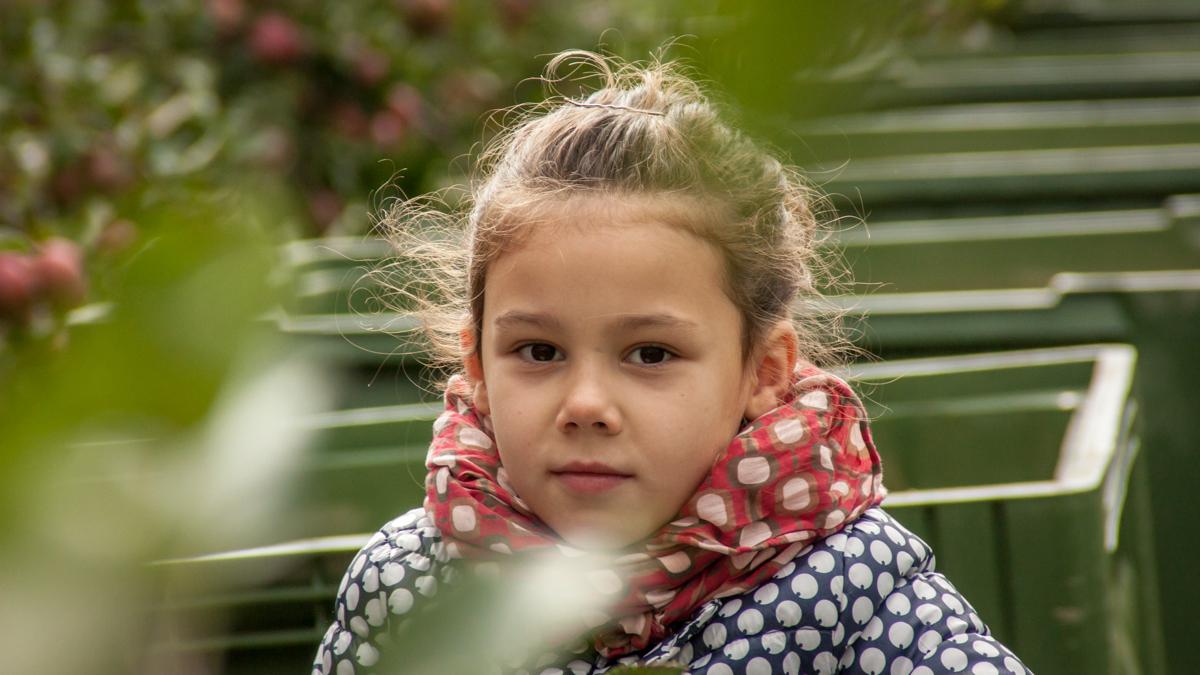 En flicka med ett äppelträd i bakgrunden