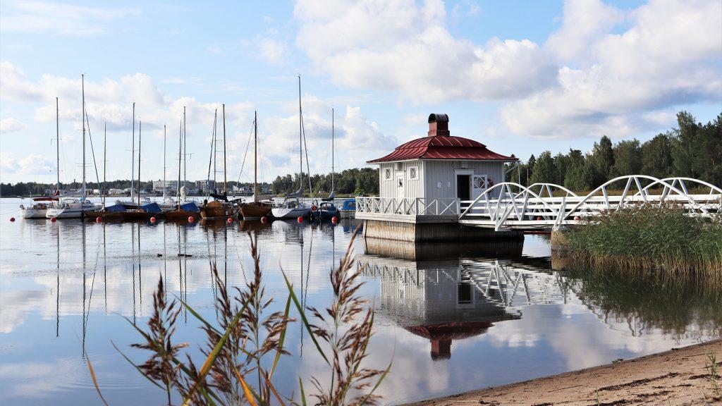Rannalta päin otettu kuva nuorisokeskus Villa Elban laiturisaunasta. Saunan takana venelaiturissa on lukuisia purjeveneitä. Taustalla olevalla vastarannalla näkyy metsää.