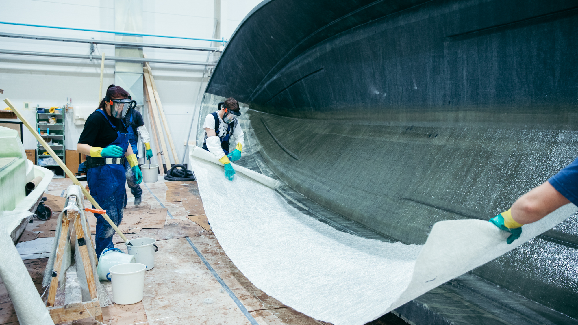 Työntekijät valmistavat venettä tehtaalla.