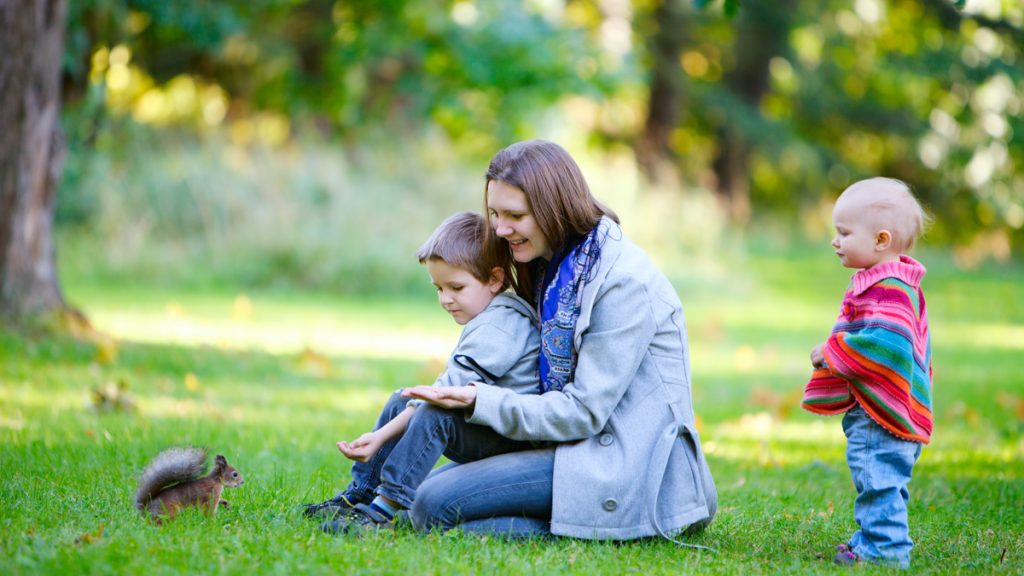Nainen ja lapset katsovat oravaa