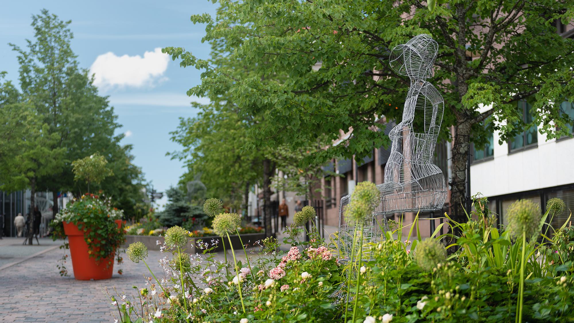 Vy över grönskande Fabriksgatan. I förgrunden blomplanteringar samt en ståltrådsskulptur som föreställer en sittande kvinna. Längre bak mera blomplanteringar samt träd som kantar gatan.