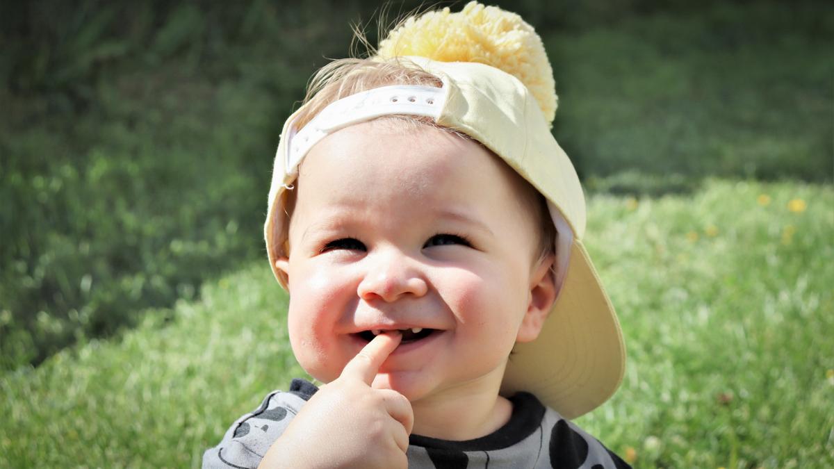 Pikkulapsi hymyilee sormi suussa