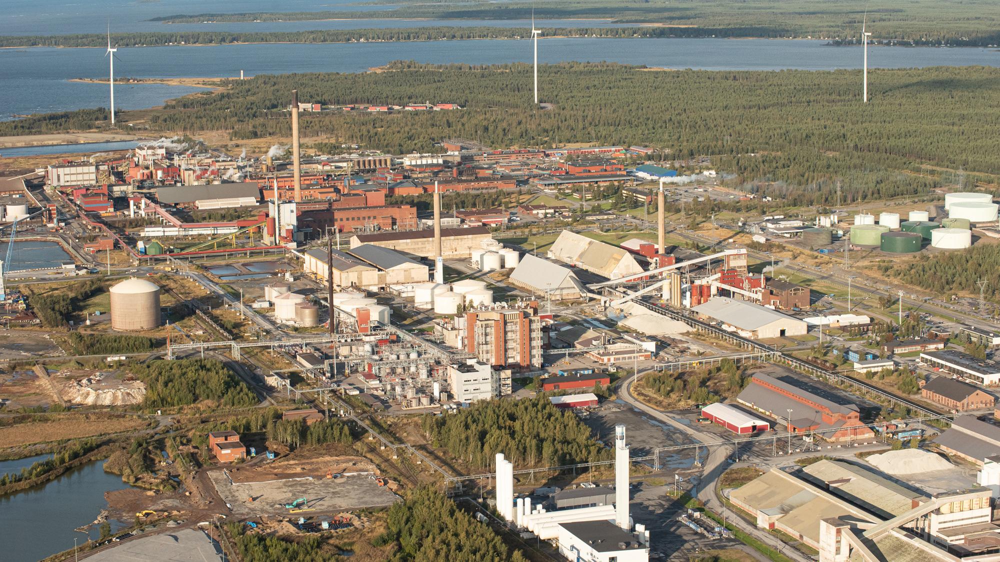 Yläviistosta kuvattu näkymä Kokkolan suurteollisuusalueesta tehdasrakennuksineen. Taustalla näkyy metsää tuulimyllyineen ja kauempana näkyy meri.