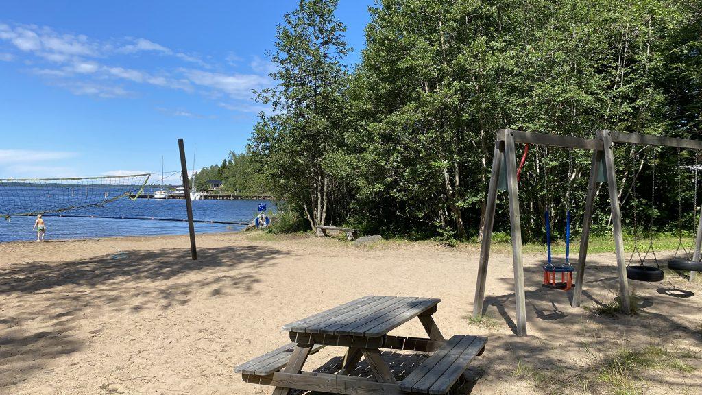 Långön ranta Öjassa. Kuvan vasemmassa laidassa näkyy rantalentopallokenttä, jonka takana siintää meri ja rantavedessä kahlaava uimari. Keskellä, kuvan etualalla on puinen pöytä penkkeineen ja sen oikealla puolella puurakenteisia keinuja. Kuvan taustalla kasvaa paljon puita.