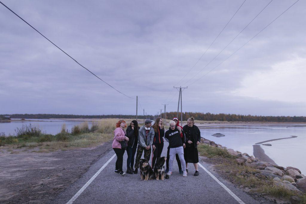 Joukko eri-ikäisiä on kokoontunut Ohtakariin vievälle tielle mukanaan muutama koira.