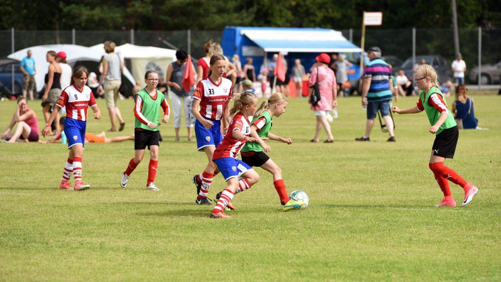 Tytöt pelaamassa jalkapalloa nurmikentällä, Kokkola Cup -turnauksessa. Kuvan keskellä vihreään liiviin ja mustiin shortseihin pukeutunut tyttö kuljettaa palloa ja hänen kannoillaan palloa tavoittelee punavalkoraidalliseen paitaan ja sinisiin shortseihin pukeutunut tyttö. Heidän ympärillään on molempien joukkueiden pelaajia ja kuvan taustalla näkyy peliä katsovia ihmisiä.