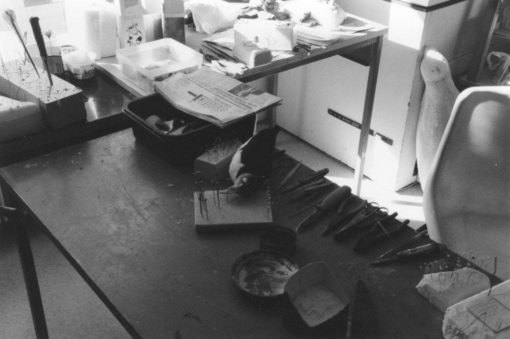 Työpöytä, jossa on mm. pinsettejä, veitsi, sakset, hohtimet ja oikopihdit. Lisäksi keskeneräisenä työnä lunnilintu.