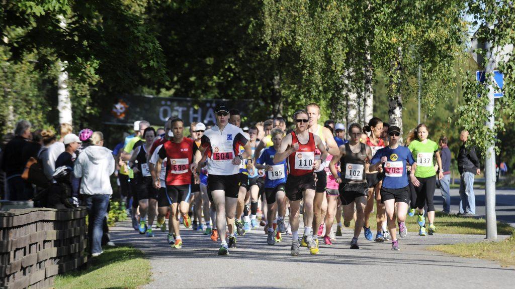 Suuri joukko juoksijoita juoksee puiden katveessa kameraa kohti. Juoksijoilla on numerolaput paidoissaan. Juoksijoiden joukossa on miehiä, naisia ja lapsia. Kuvan vasemmassa laidassa on aita, jonka takana on ihmisiä juoksua katsomassa.