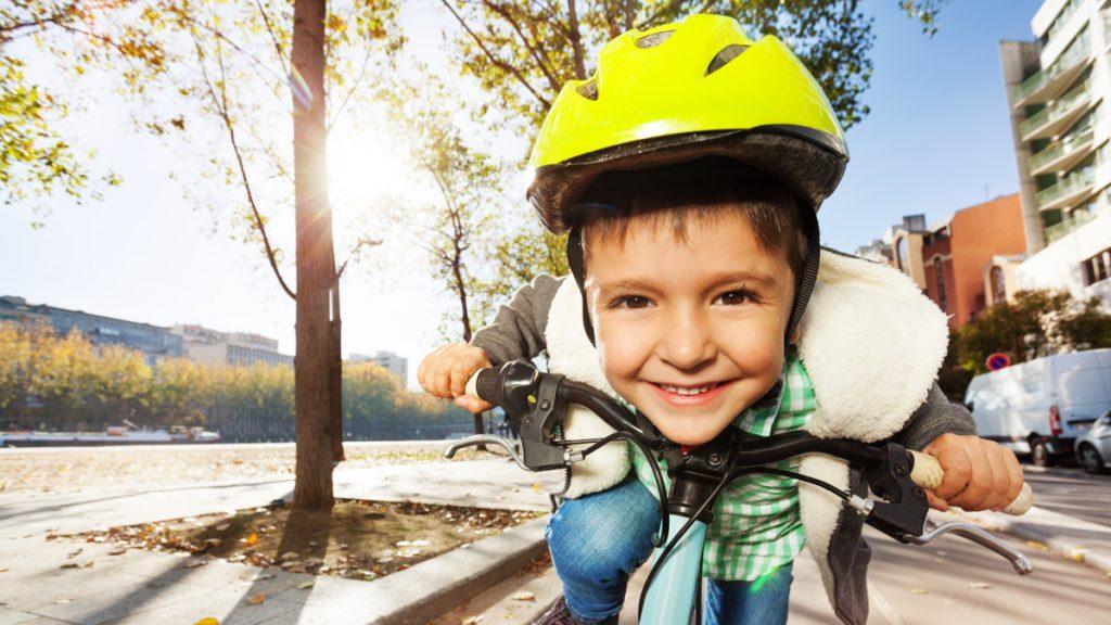 Poika hymyilee iloisesti pyöräilykypärä päässään.
