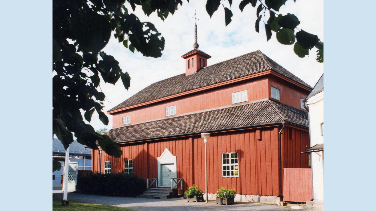 Punainen, puinen vanha koulurakennus kesällä kuvattuna.
