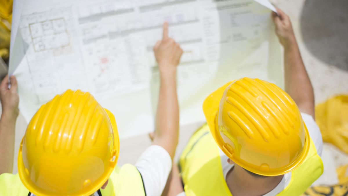 Kypäräpäiset rakentajat tutkivat piirrustuksia