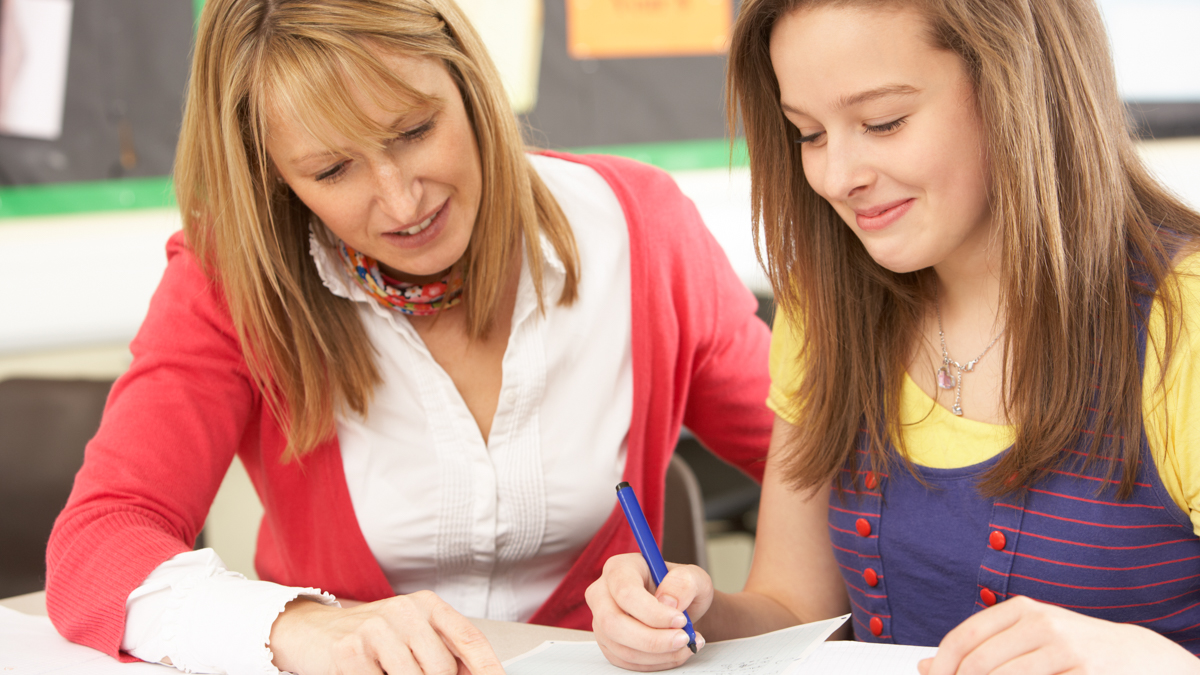 A teacher and a pupil are working on an assignment.