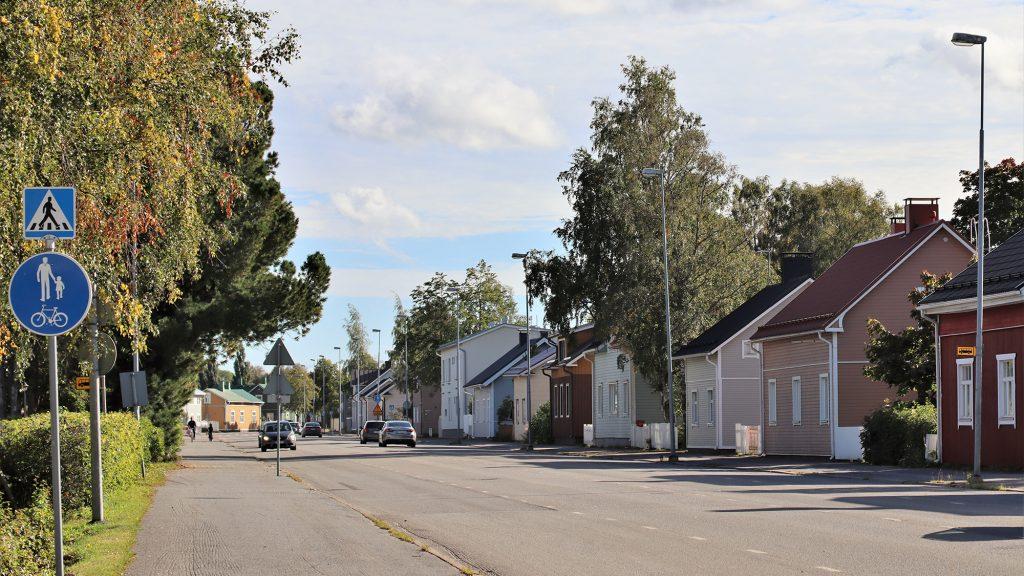 Katunäkymä Kustaa Aadolfinkadulta. Kuvan etualalla kulkee kaksisuuntainen tie, jossa kulkee useita autoja. Kuvan oikeassa reunassa, tien takana näkyy monenvärisiä rintamamiestaloja ja niiden pihoissa kasvavia lehtipuita.
