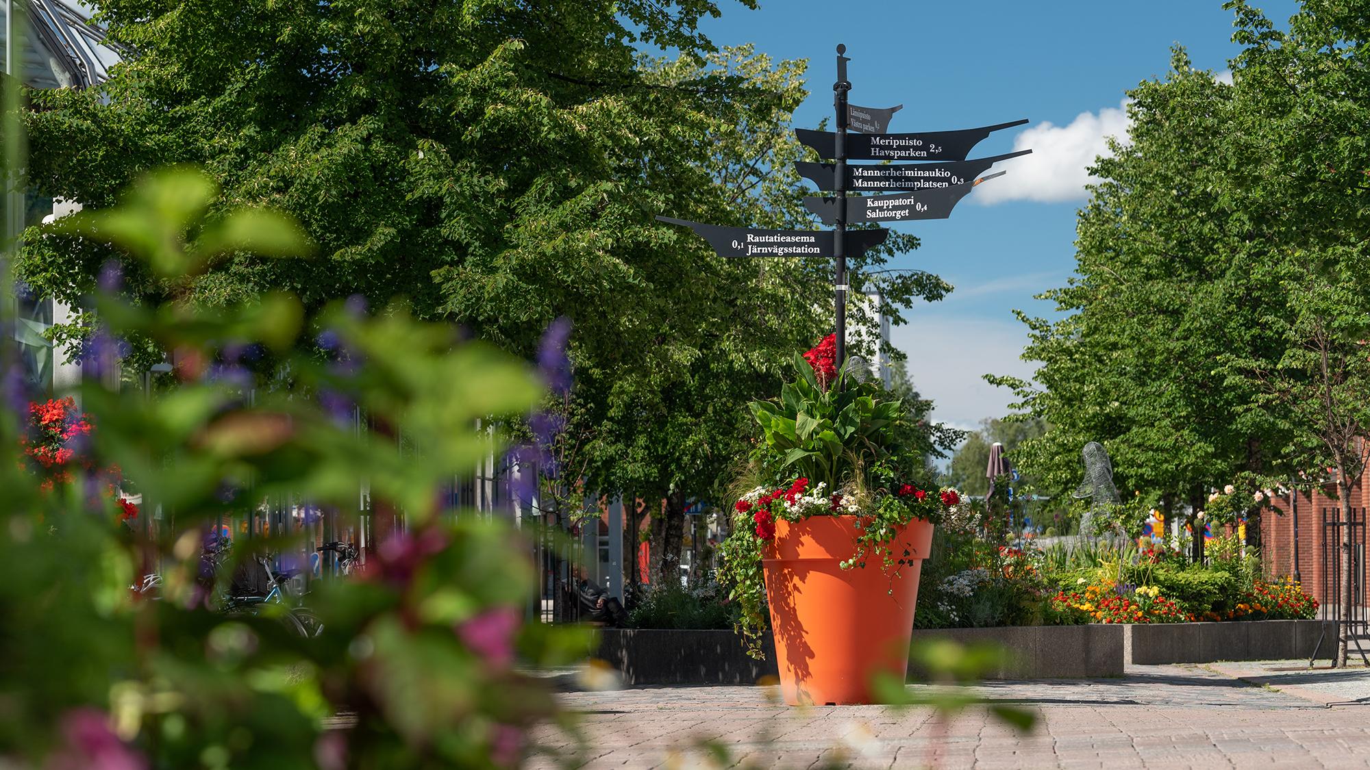 Näkymä istutuksia täynnä olevalle Tehtaankadulle. Kuvan keskellä on kukkia tulvillaan oleva suuri kukkaruukku, jonka keskeltä nousee musta, metallinen, moneen eri suuntaan viittova opaskyltti.