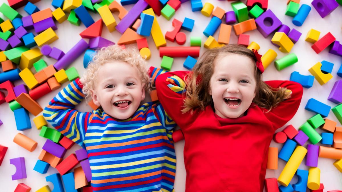 Kaksi lasta värikkäiden palikoiden keskellä