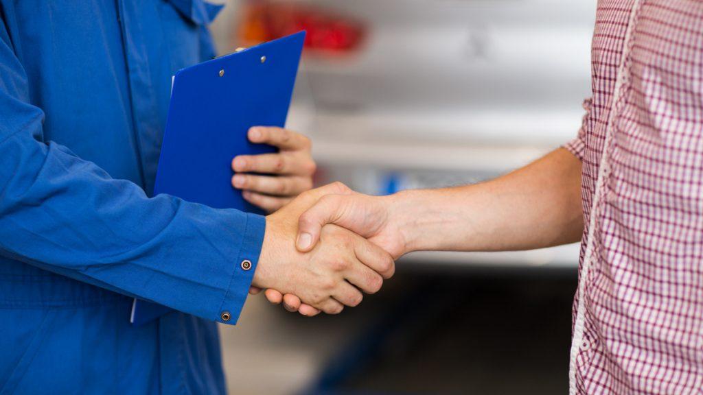 Siniasuinen henkilö kättelee ruutupaitaista henkilöä.