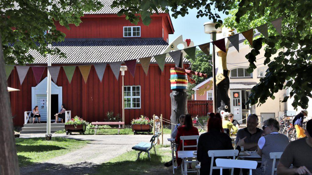 Kesäinen näkymä museopihasta. Taustalla näkyy punainen Pedagogio, jonka aukinaisten ovien molemmin puolin istuu kaksi naista tuoleillaan. Etualalla, kuvan oikeassa reunassa on joukko pöydissä istuvia ihmisiä ja heidän yläpuolellaan, puiden katveessa kulkee monivärinen viirinauha.