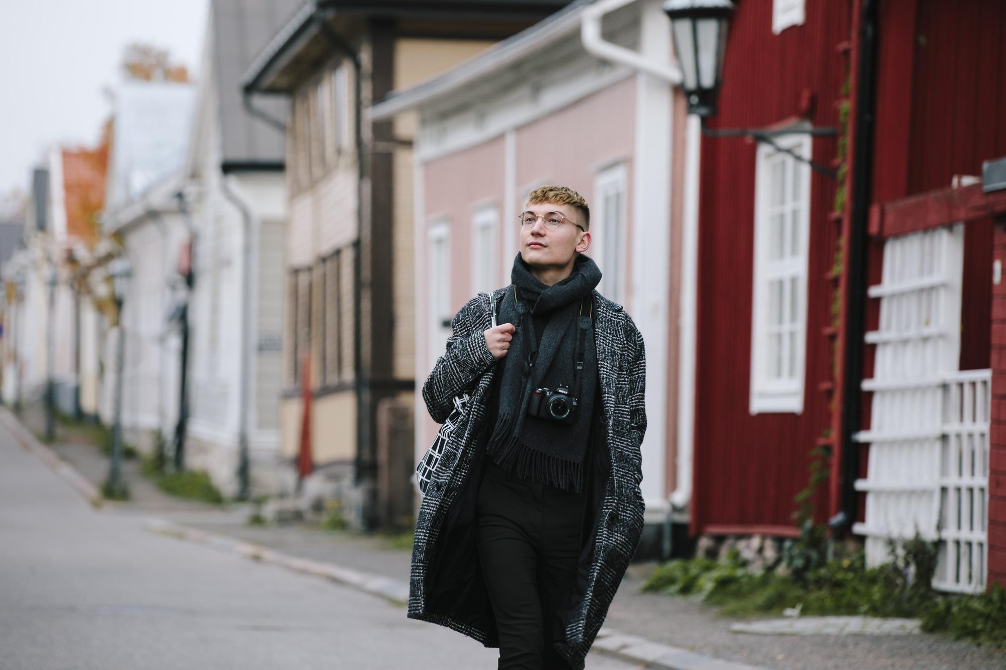 Nuori kävelee katsellen Neristanin värikkäitä taloja.