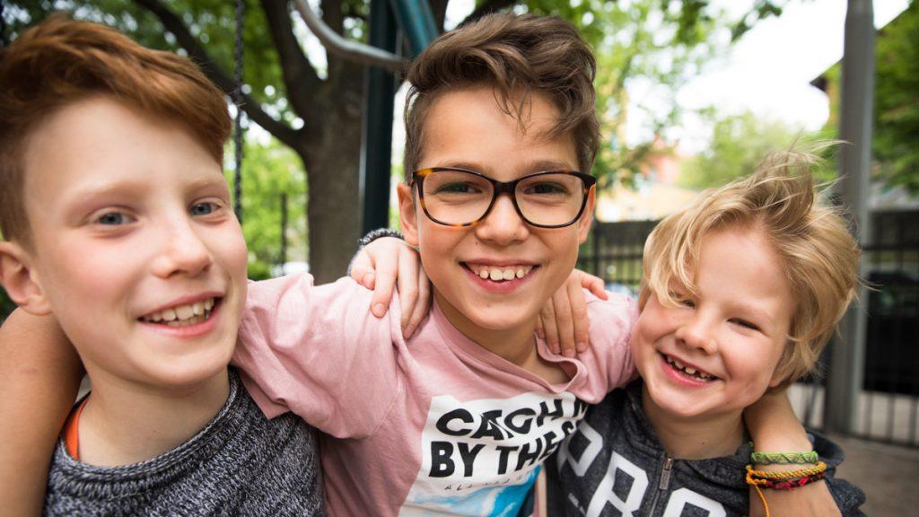 Kolme koululaista hymyilee ulkona