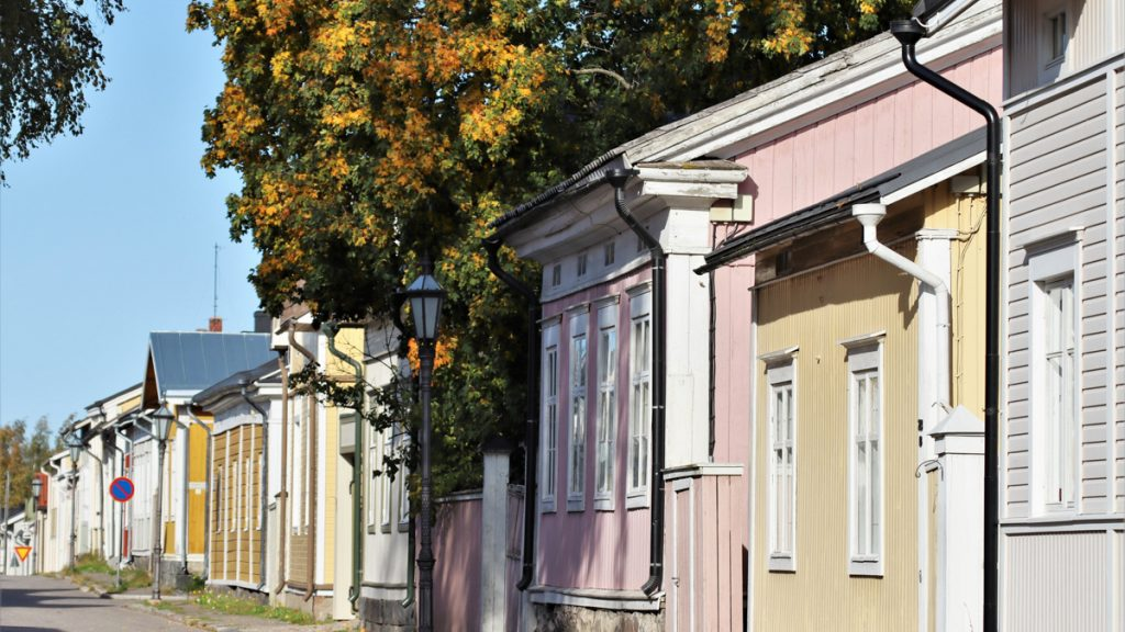 Rivi värikkäitä puutalojen julkisivuja vanhassa kaupungissa