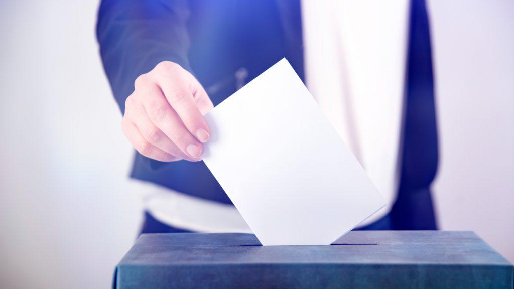 Käsi pudottaa äänestyslipúkkeen uurnaan