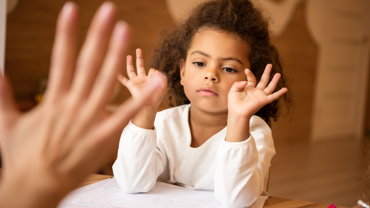 A little girl is learning to count with fingers.