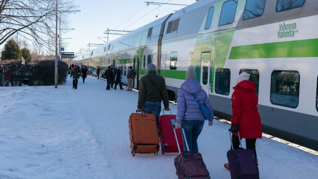 Ihmisiä menossa junaan matkalaukkujen kanssa