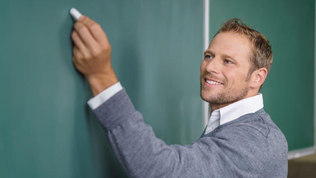 Opettaja kirjoittaa liitutaululle