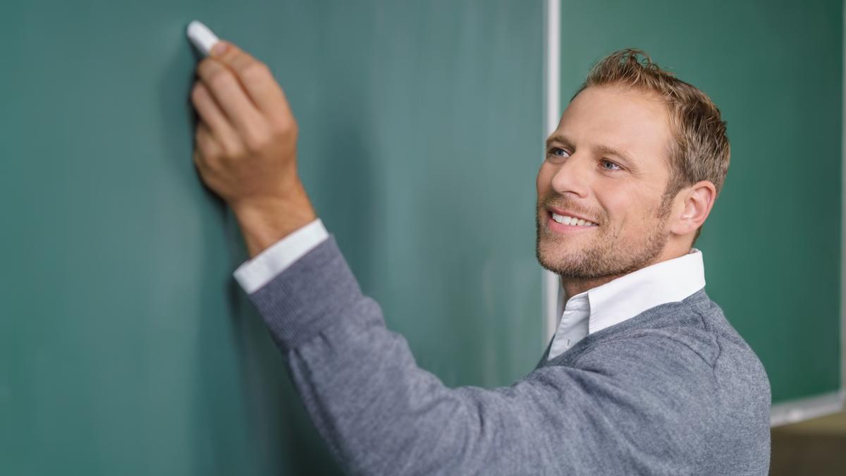 A teacher writing on chalkboard.