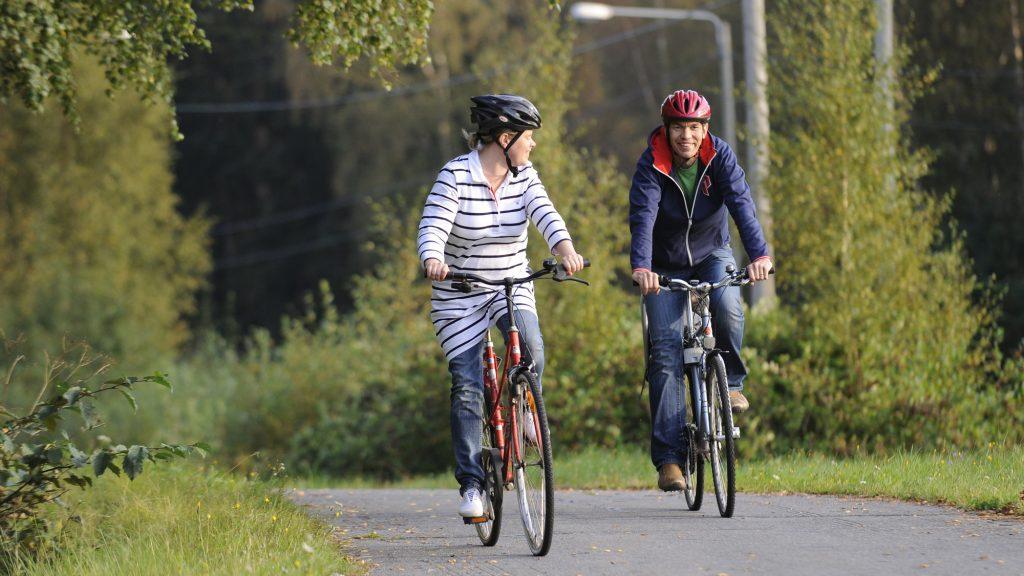 Nainen ja mies pyöräilevät pyörätietä pitkin. Hieman edempänä ajava nainen on pukeutunut raidalliseen tunikaan, farkkuihin ja valkoisiin tennareihin. Taaempana tuleva mies on pukeutunut farkkuihin ja tummansiniseen huppariin, joka on osittain auki. Kummallakin on pyöräilykypärä päässään. Nainen katsoo hymyilevään mieheen päin. Taustalla näkyy vehreitä lehtipuita.