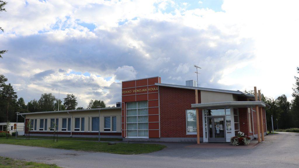 Veikko Vionojan koulurakennus kesäisenä pilvisenä päivänä.