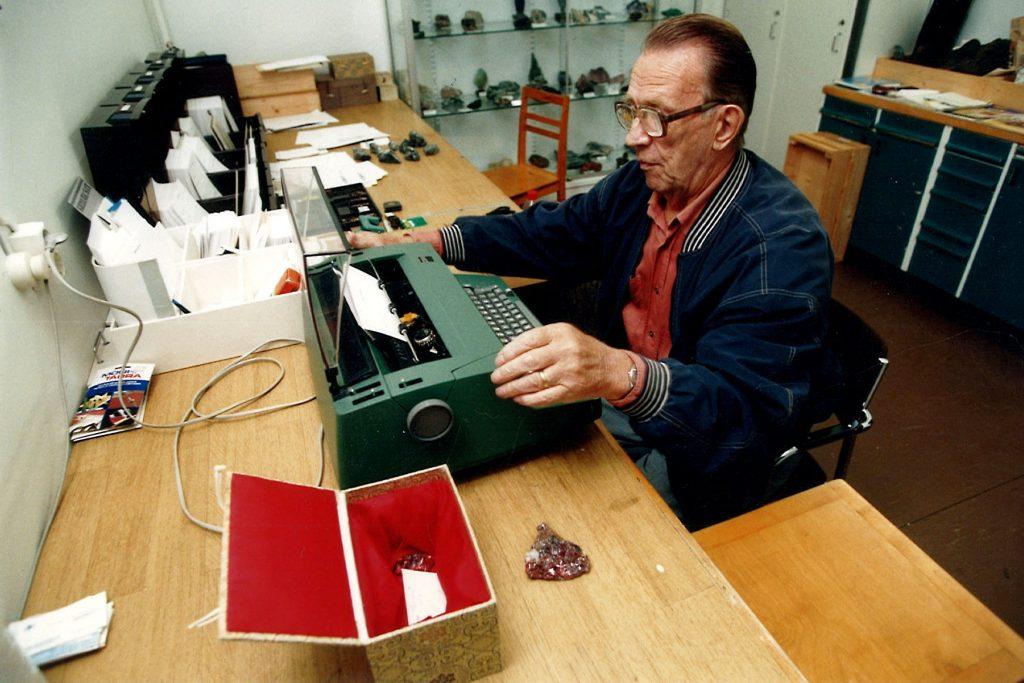 Nissinen kirjoituskoneensa ääressä. Vieressä pöydällä on mahdollisesti Kiinasta tullut koristeellinen laatikko mineraalinäytteineen.
