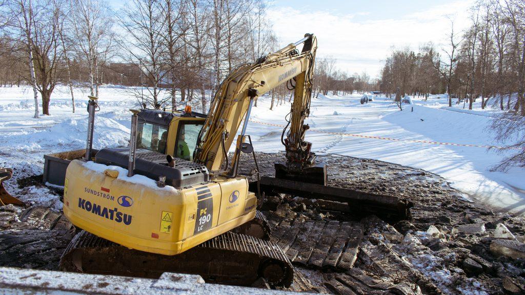 Etualalla keltainen kaivinkone ruoppaamassa lumen ja jään peittämää Suntia. Taustalla näkyy lumen peittämä ja puiden reunustama Sunti.