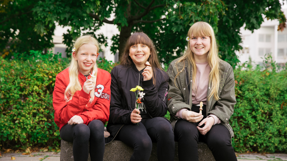 Kolme nuorta tyttöä katsoo kohti