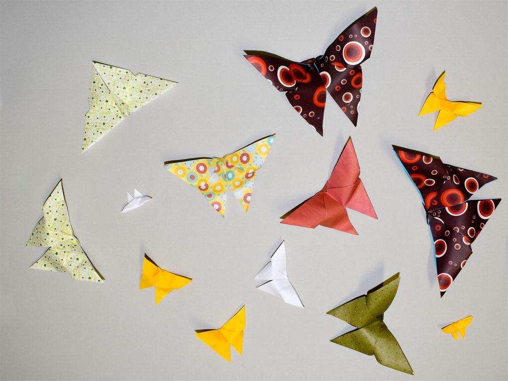 Värikkäistä papereista taiteltuja perhosorigameja pöydällä.