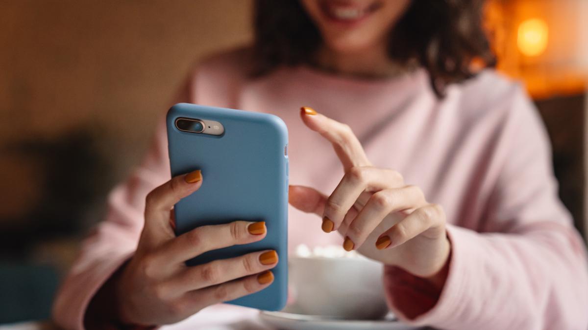 En kvinna använder en mobiltelefon.