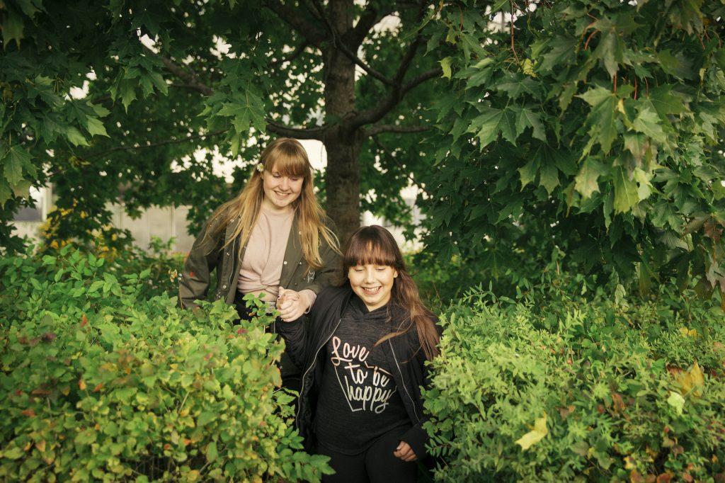 Kaksi tyttöä tulee hymyillen kasvillisuuden seasta.