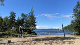 Långön ranta Öjassa. Kuvan etualalla näkyy rantahietikolla oleva lentopallokenttä. Kentän takana näkyy sininen meri ja kaksi rantavedessä kävelevää uimaria. Kauempana näkyy laituri veneineen. Kuvan molemmilla reunoilla näkyy puita.