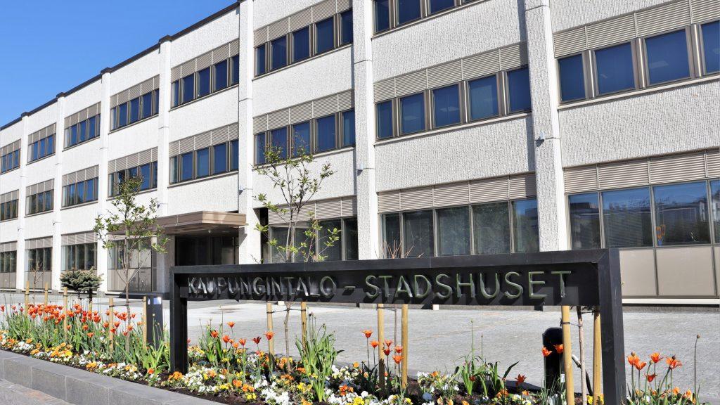 Kaupungintalon edessä olevaan kukkapenkkiin pystytetty metallinen kyltti, jossa lukee kaupungintalo, stadshuset. Kyltin takana näkyy kaupungintalo.