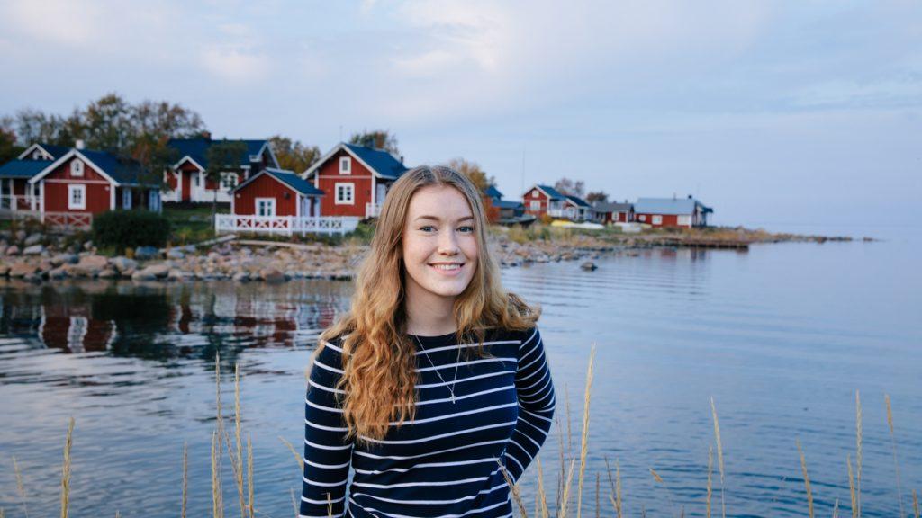 Tyttö katsoo kohti kameraa, taustalla kalastajakylä