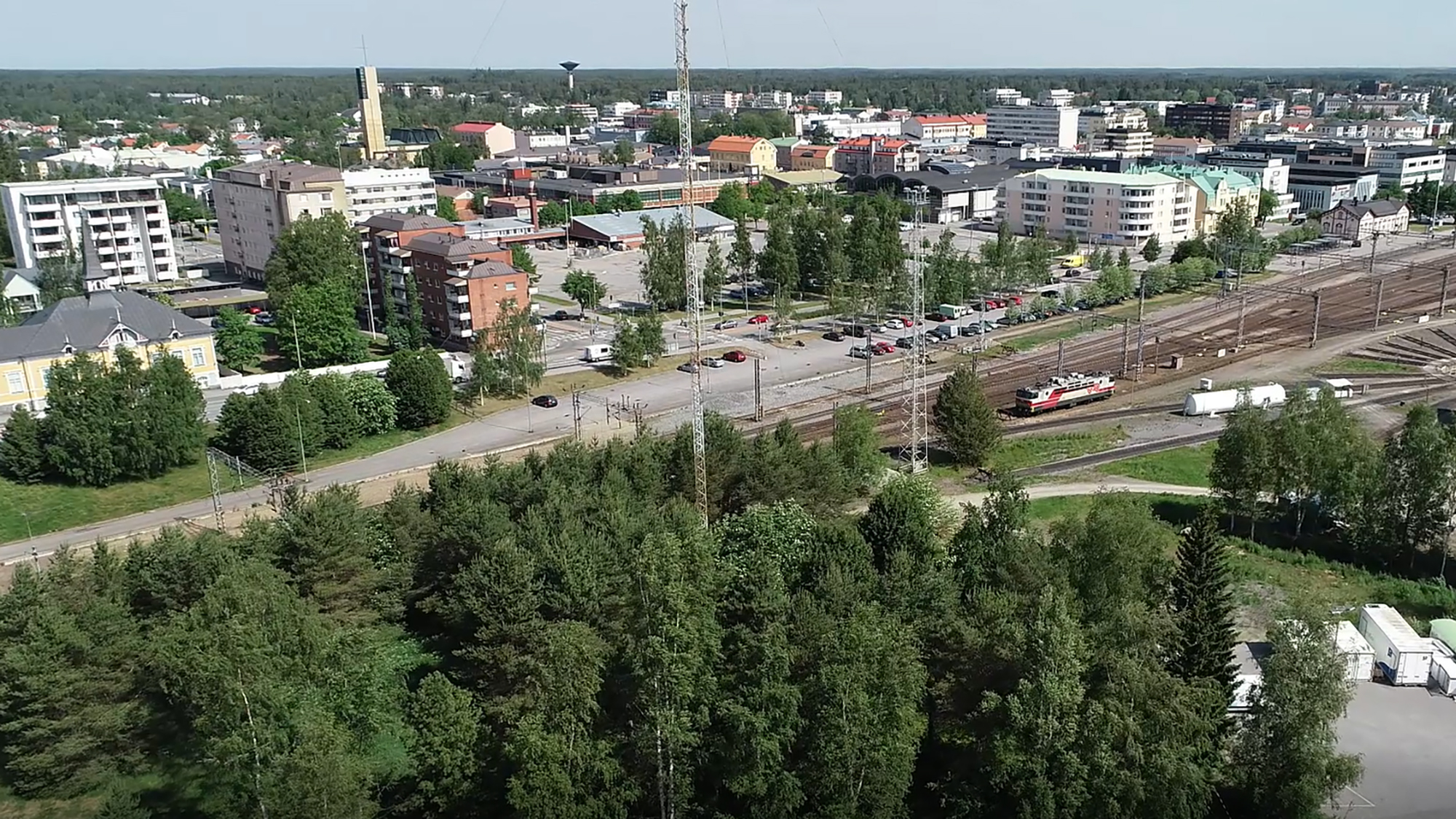 Korkealta viistosta kuvattu näkymä, jonka etualalla on puita ja niiden takaa aukeaa näkymä rautatieaseman ratapihalle sekä sen takana aukeavalle kaupungille rakennuksineen. Kaukana horisontissa näkyy myös Kokkolan vesitorni.