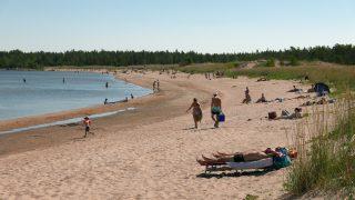 Vattajan hiekkaranta auringonottajineen sekä meressä uimassa olevia ihmisiä. Hiekkarannan takaa kohoaa metsä.