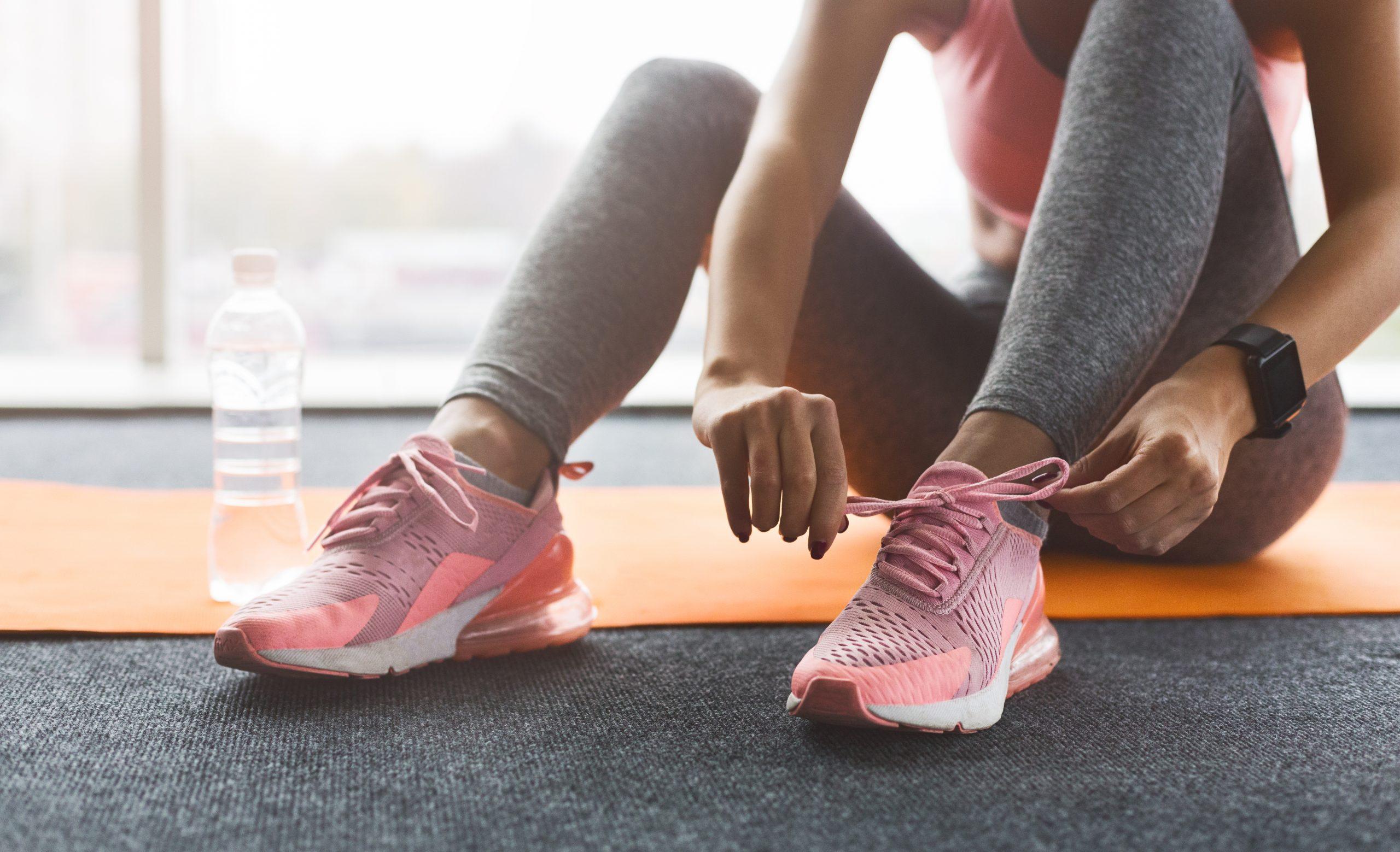 Kuvassa jumppamatto, juomapullo ja nainen sitomassa lenkkarit jalkaan
